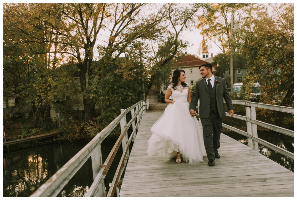 wedding couple walks together on a bridge during sunset in Wisconsin