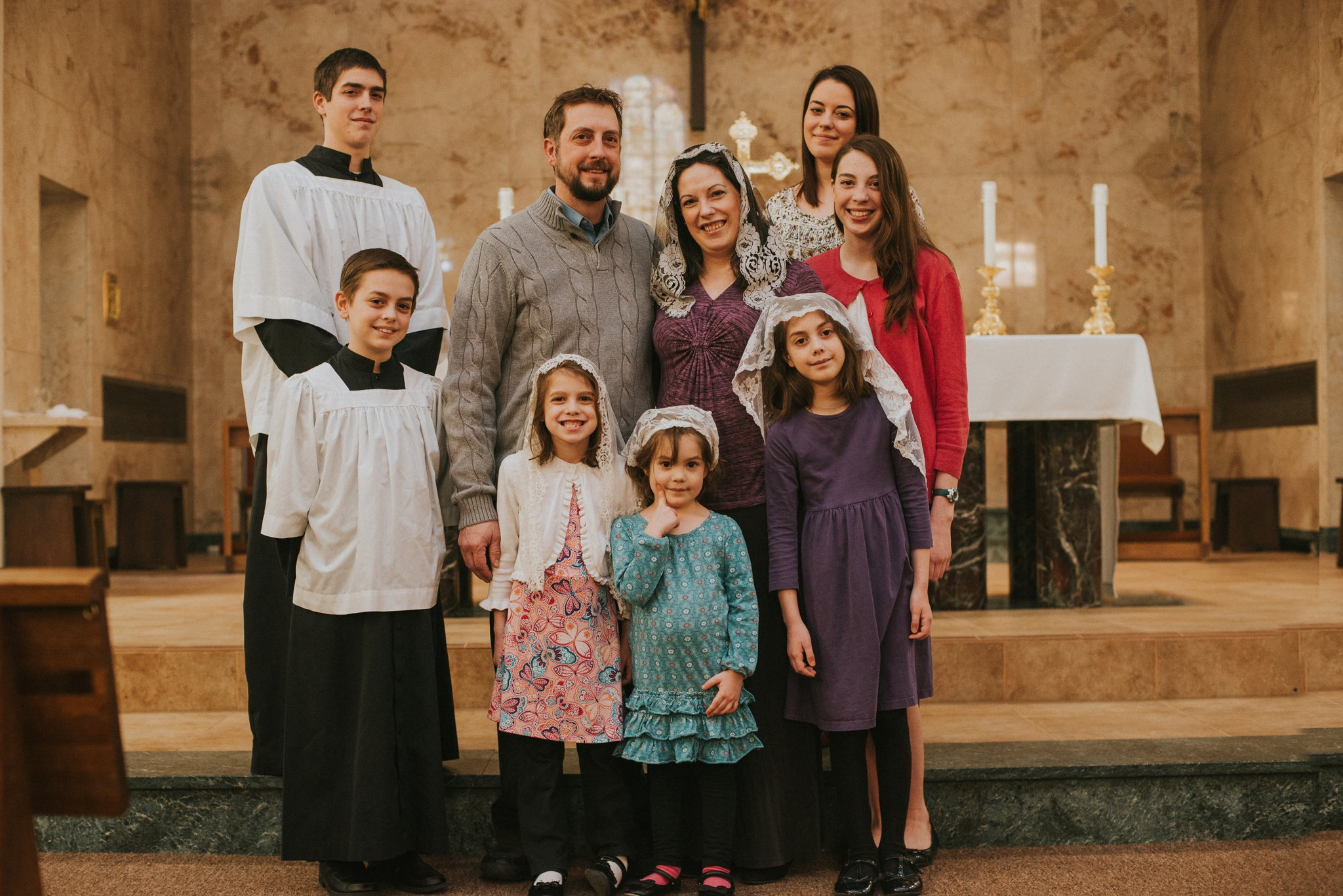 Family of 9 stand together at a church alter