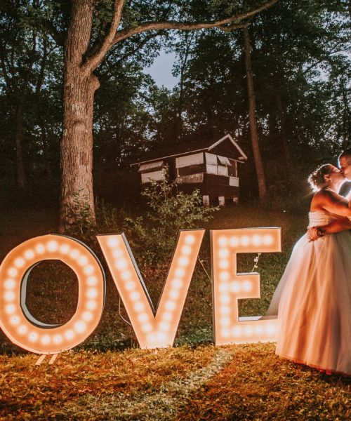 DIY wedding couple standing near their homemade sign.