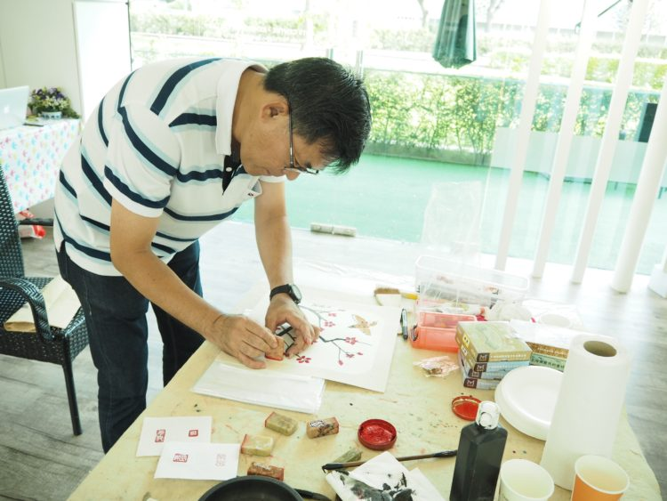 Art instructor teaching composition of seal carving on Chinese ink painting artwork