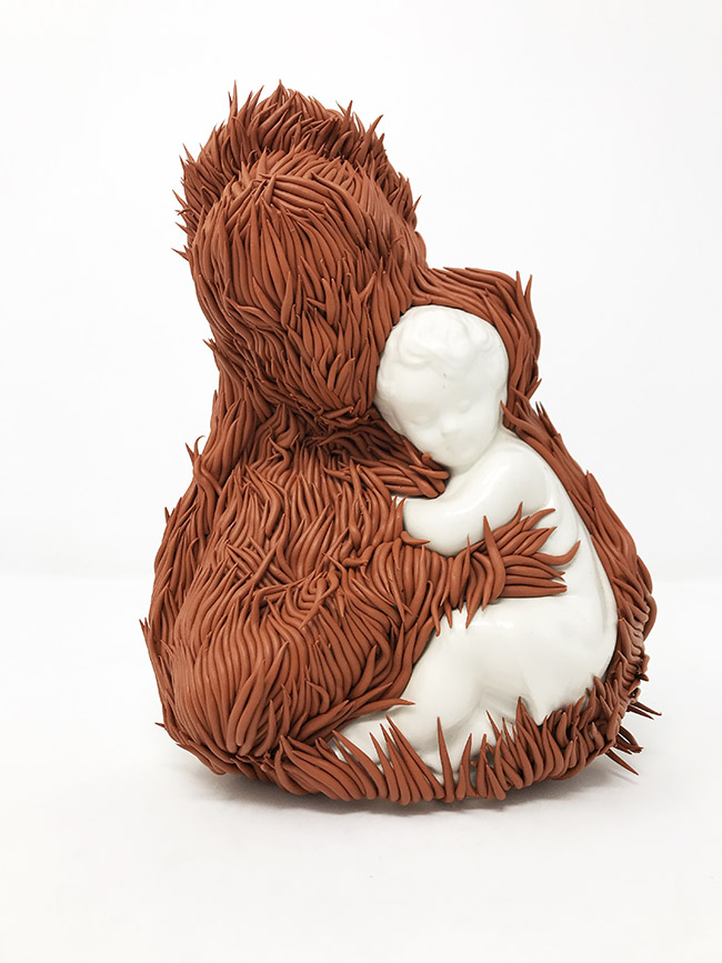 "Sculpture by Andrèa Keys Connell. ""Feathers Fall, Grass Grows"", Found ceramic figurine, polymer clay, 12"" x 8"" 6"""
