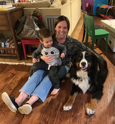 Shelby sitting on floor holding friend's son and next to dog Jackson
