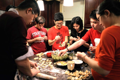 Rui's family gathered around a table making dumplings