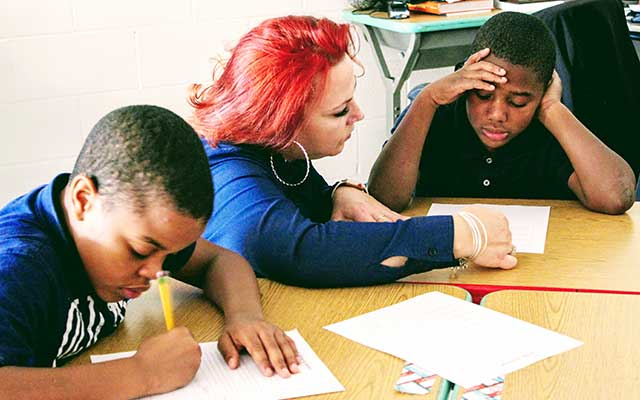Teacher with red hair helping two African-American male students