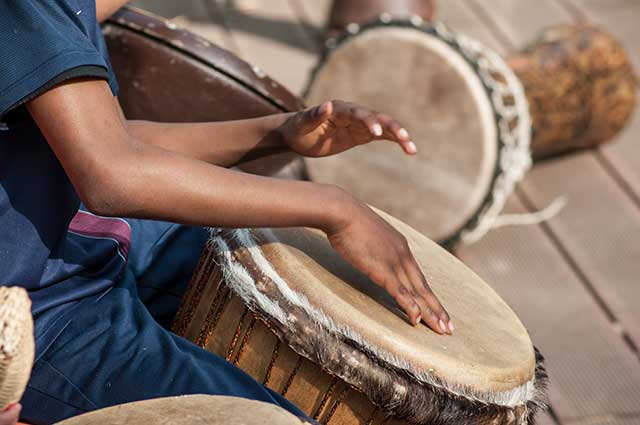 Drummer surrounded by African drums