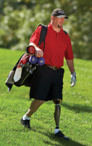 Man carrying a golf bag wearing a prosthetic leg, on services page of Saunders Prosthetics and Orthotics Group website