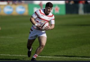 Rugby player in a striped jersey holding a rugby ball on an outdoor field