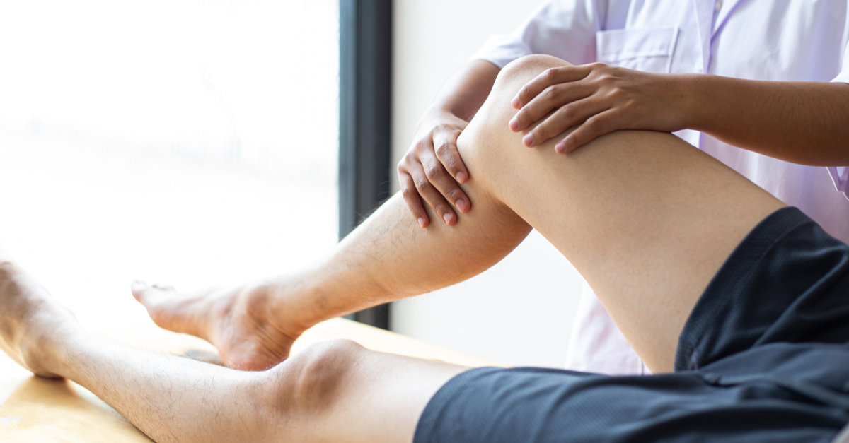 a chiropractor massaging the right foot of a man