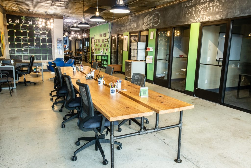 A photo taken inside the Biz Foundry's Cookeville coworking space. A wooden tale with mugs filled with pens and markers. The table is surrounded by office chairs.