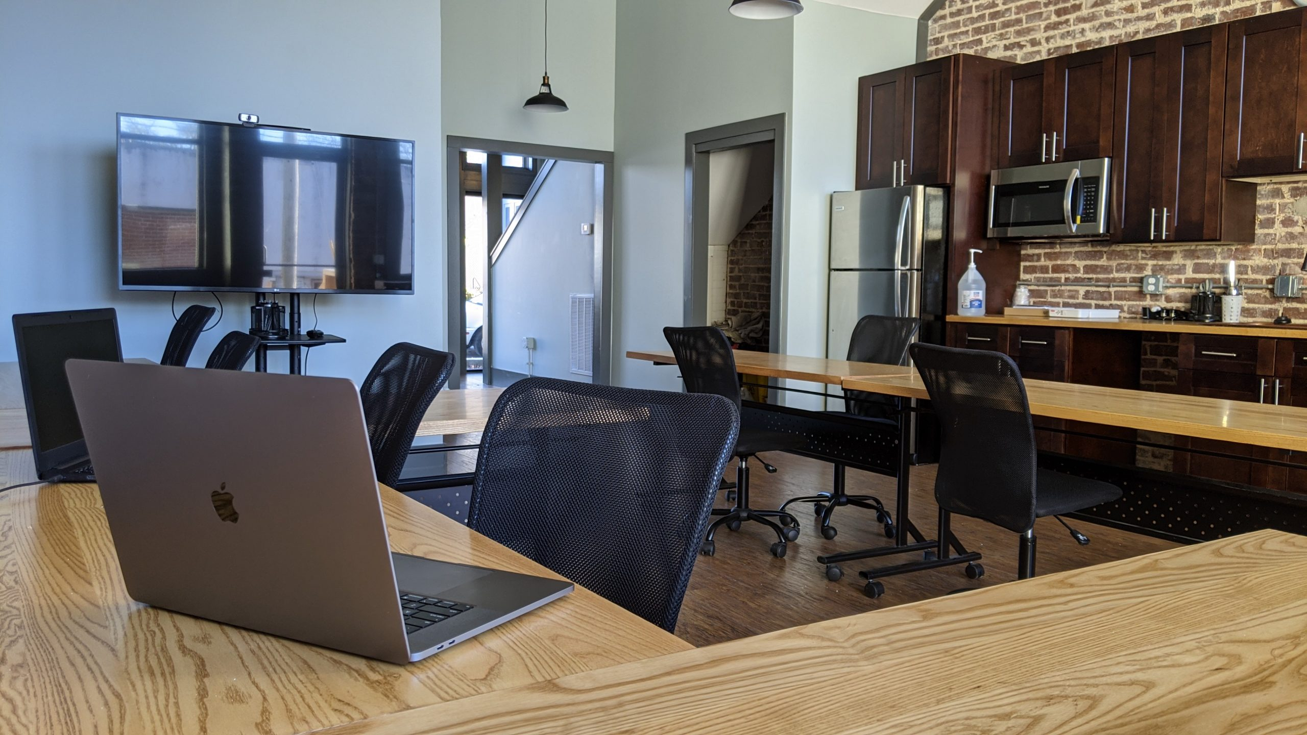 Picture of a coworking space with wooden tables, white walls, and a kitchenette.