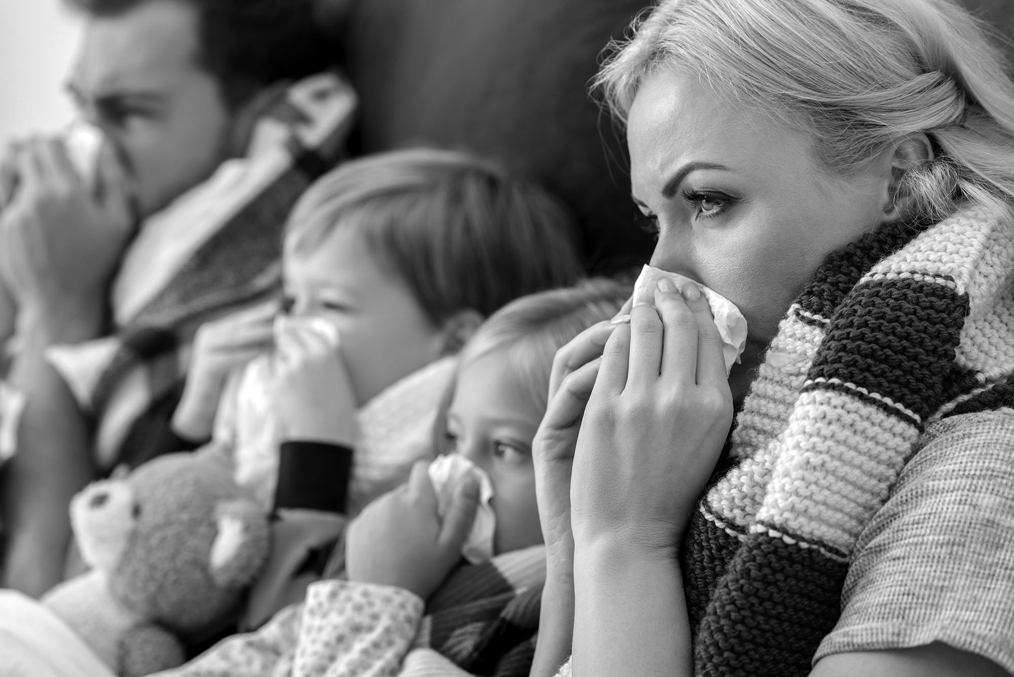 close-up shot of sick young family blowing noses with napkins together while lying in bed