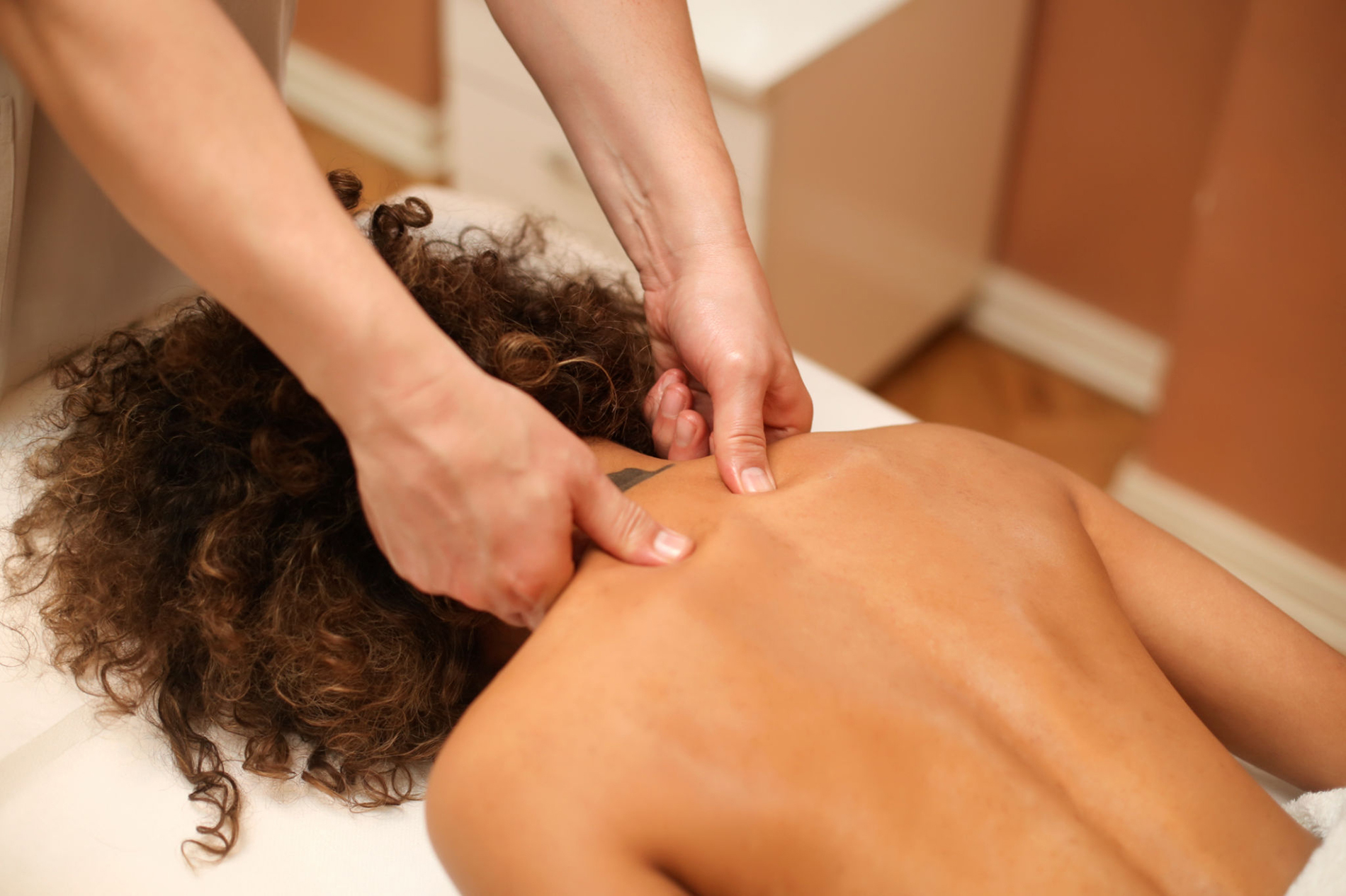 Massage treatment - neck and whole body massage by womans. doing massaging using oil. neck and whole body massage, relaxing massage, strong hands of a masseur, massage to increase work efficiency