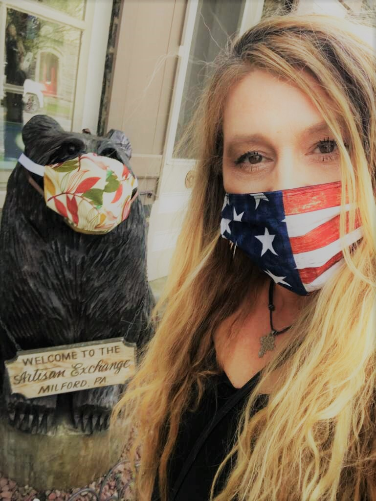 woman in black shirt with USA mask next to bear statue