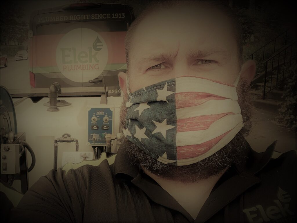 man in black shirt and USA flag mask in front of elek plumbing truck