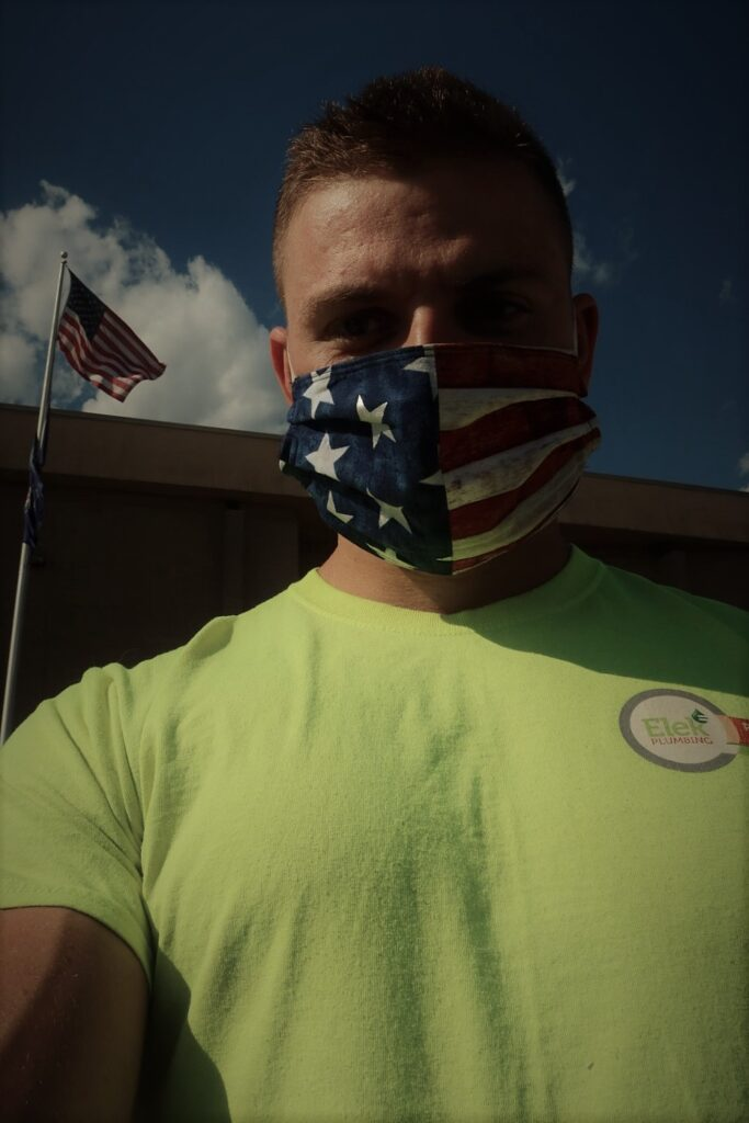 man in neon yellow shirt & USA mask with USA flag behind