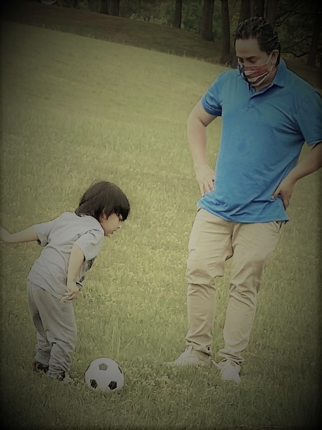 man in turquoise shirt playing soccer with small boy