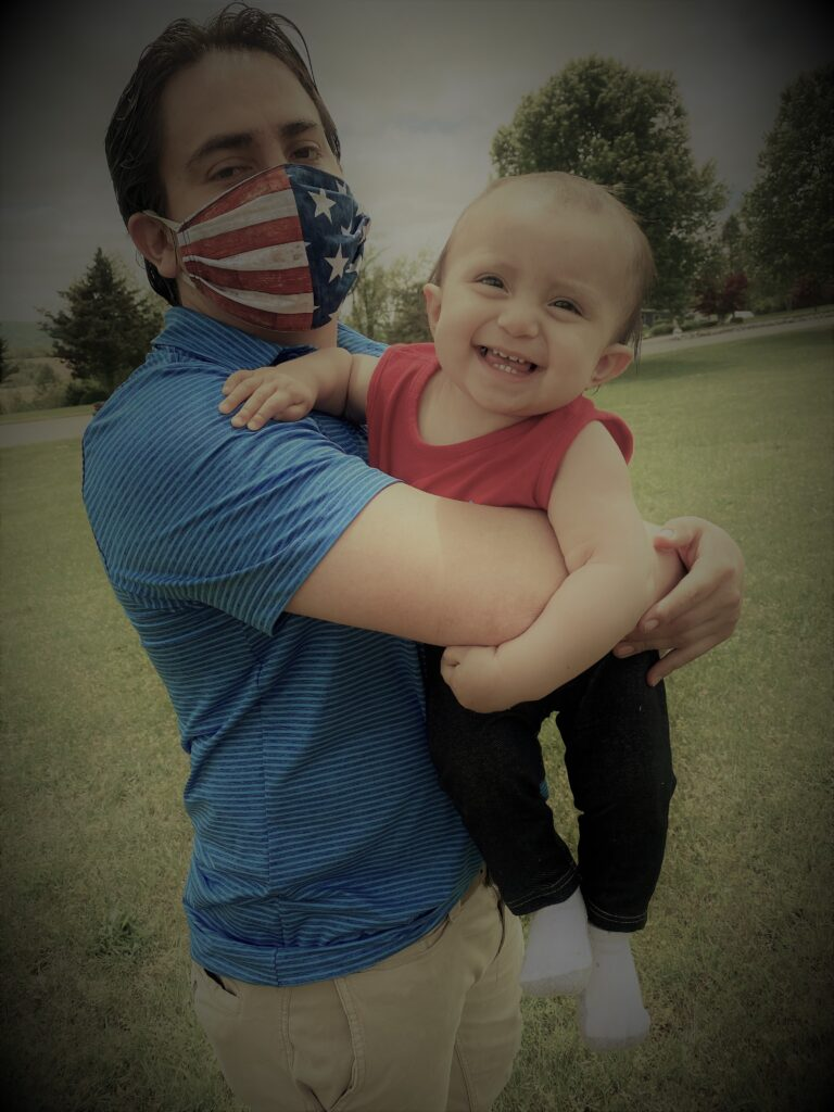 man in blue shirt & USA mask holding baby