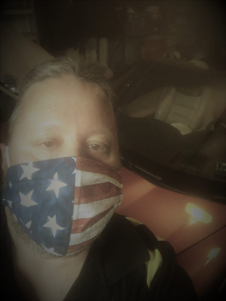 man in USA mask in front of corvette