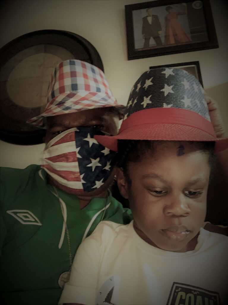 man and grandson with USA masks & fedoras