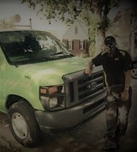man in black shirt with USA mask leaning on neon green truck