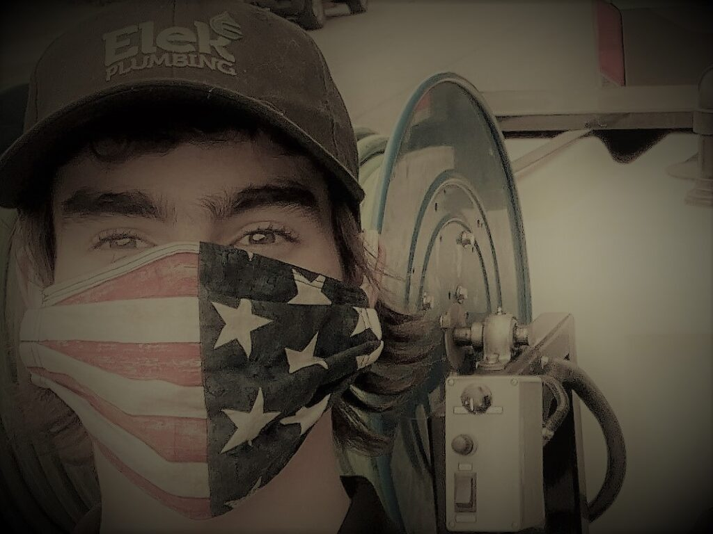 young man in USA flag mask in front of equipment