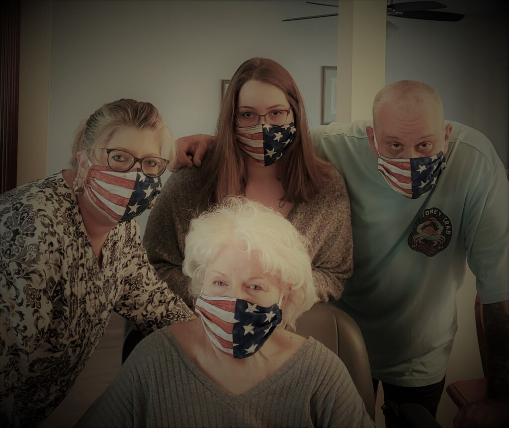three women & one man wearing USA masks