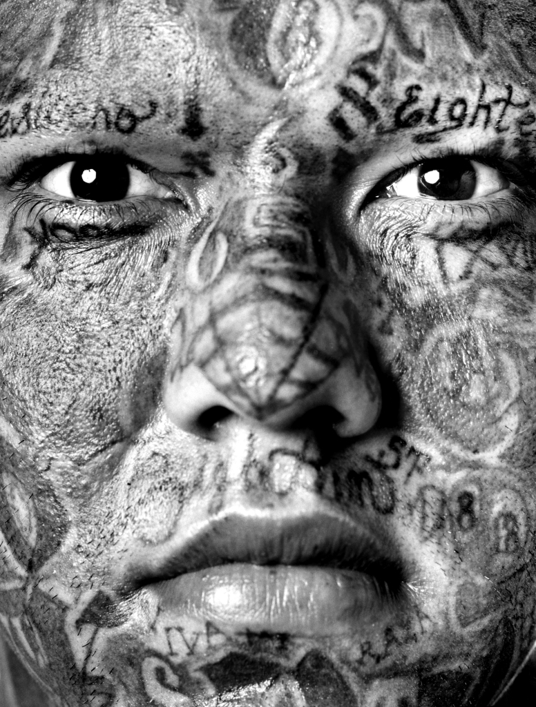 Photography of a tattooed gang member by Isabel Munoz.
