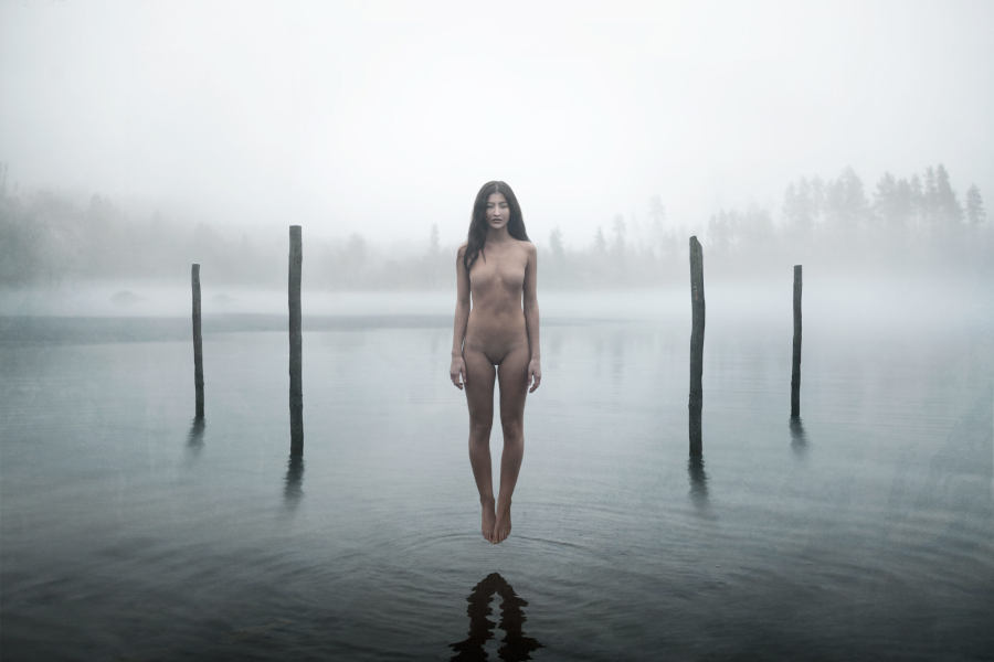 Floating nude woman above water
