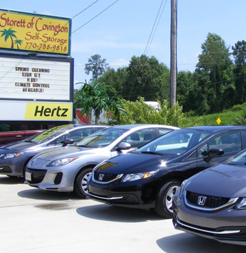 Storret of Covington has a variety of Penkse trucks for rental. We also offer Hertz car rental. Pictured: Storefront in background with moving trucks and cars in foreground