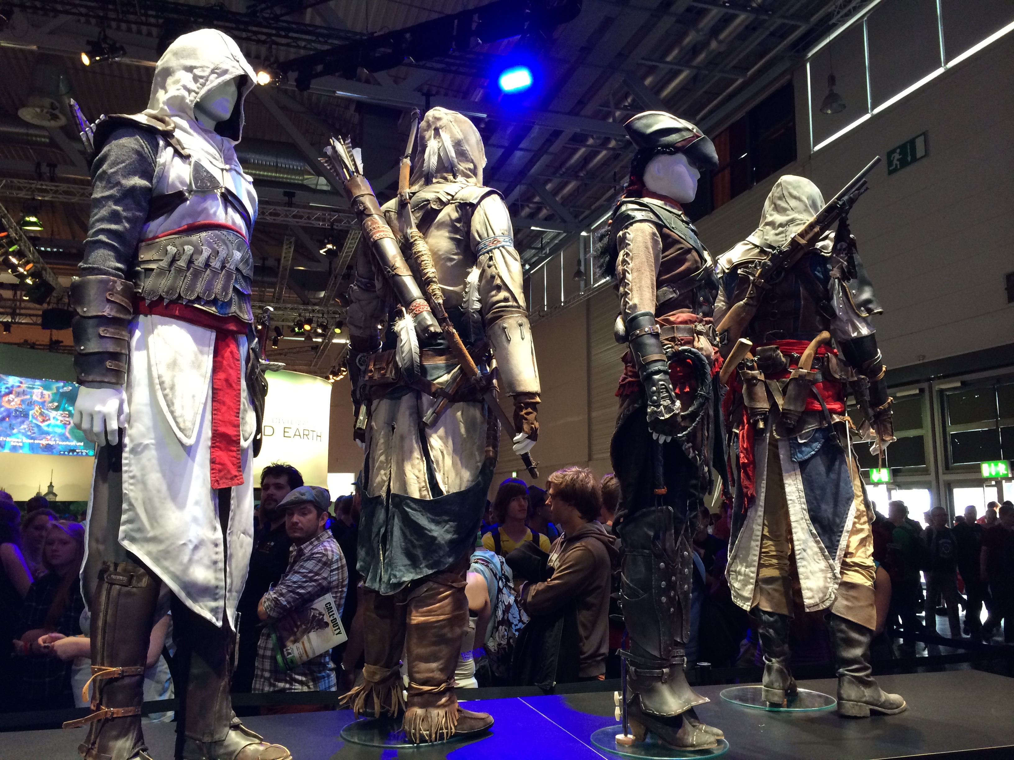 Assassin Statues on display near the Assassin's Creed: Unity and Rogue booths.