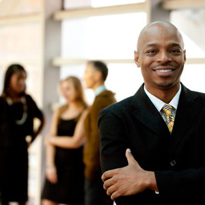 stock-photo-a-happy-black-business-man-with-people-in-the-background-47419153