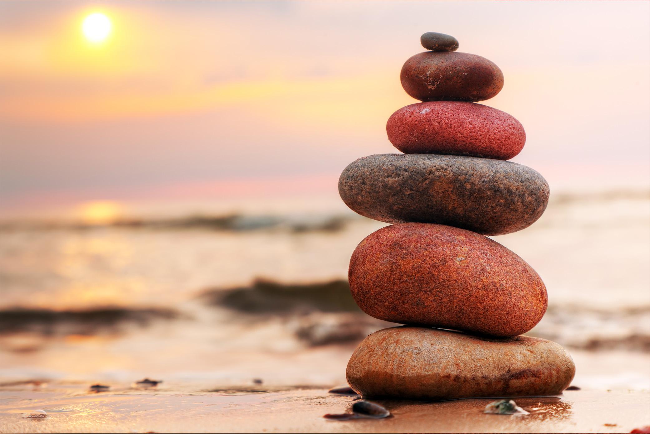Stones pyramid on sand symbolizing zen, harmony, balance-1