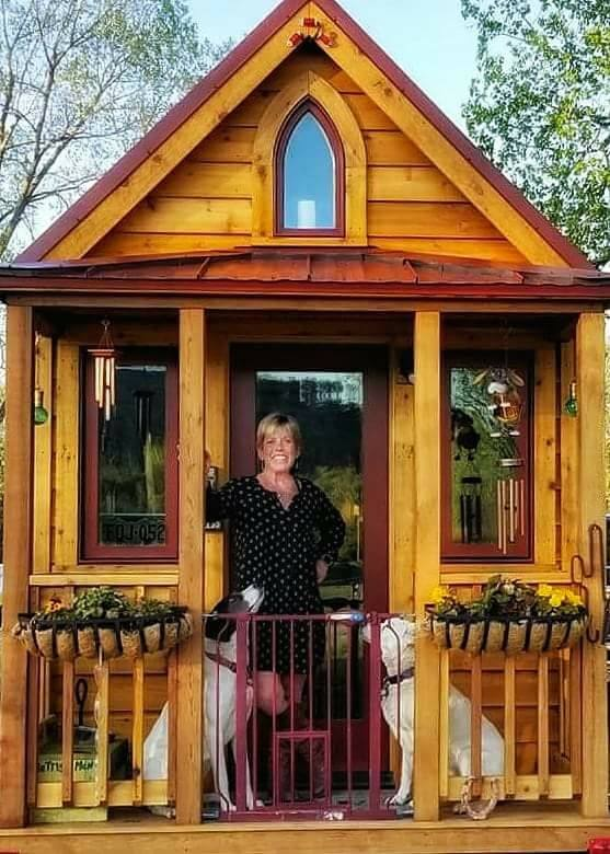 Katrina with her pups in front of her tiny house.