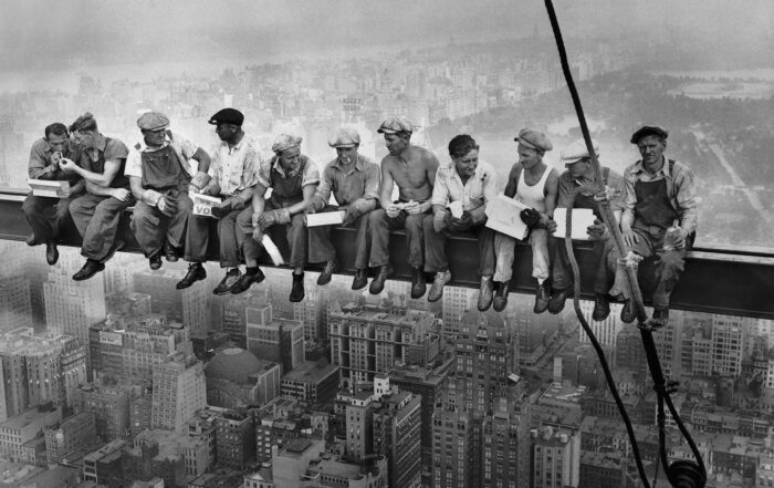 Construction workers on steel beam of Empire State Building skyscraper
