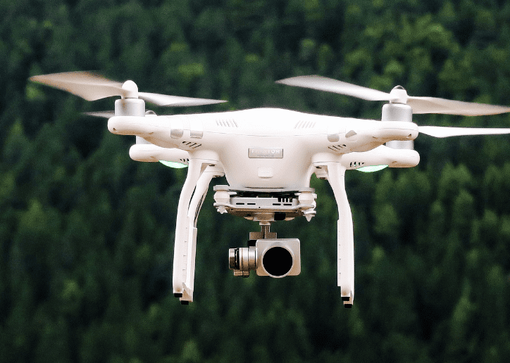Drone hovering in front of trees