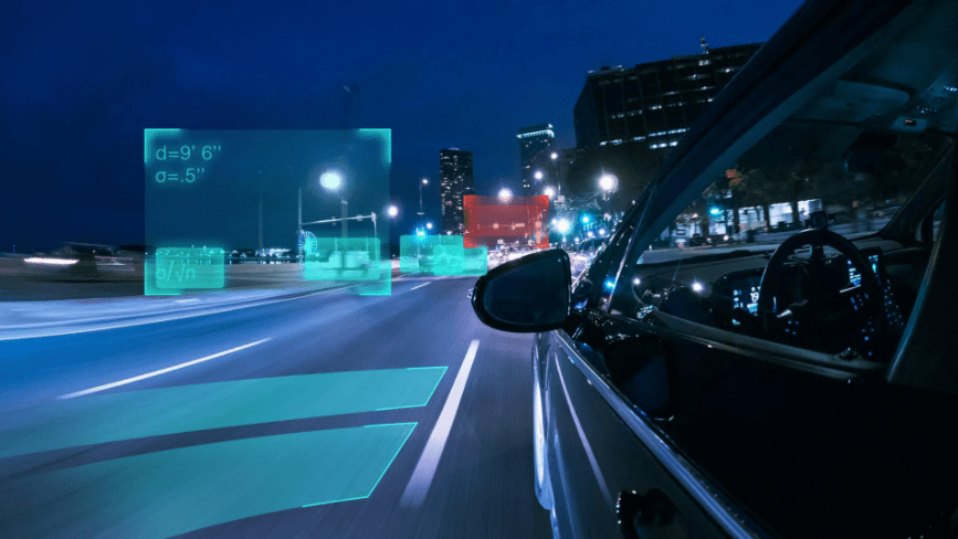 Car driving down the street in the dark