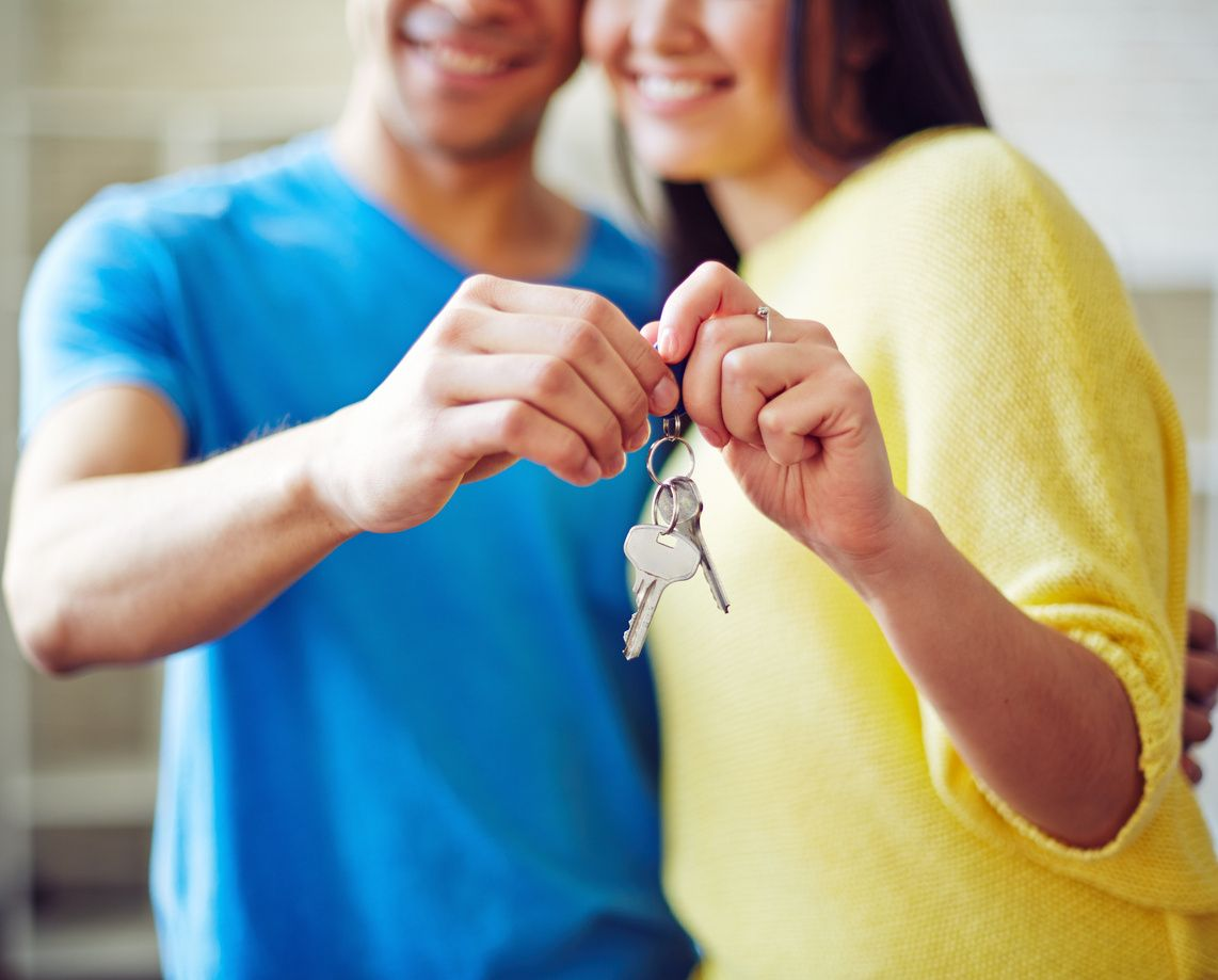 id theft buying a house couple holding a key