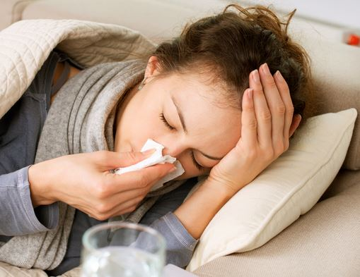 woman with kleenex over her nose