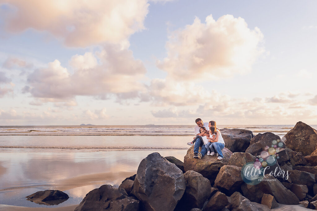 Family sitting on the rocks at a beach with beautiful clouds in the sky