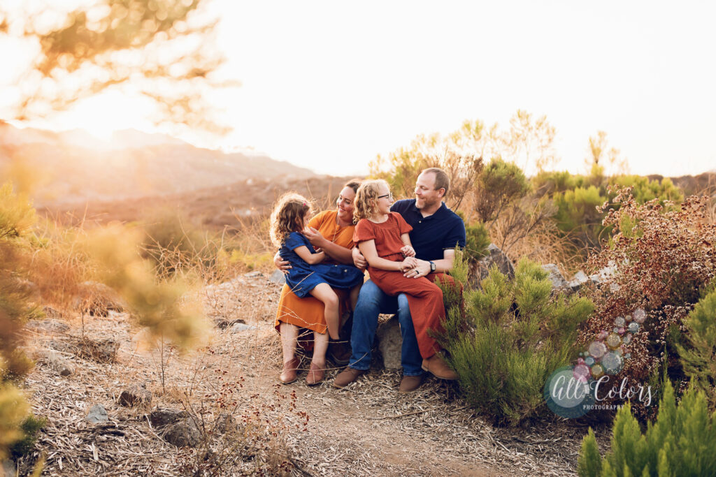 Family of four sitting on a rock at sunset