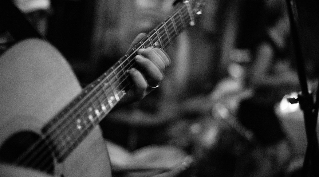 photo of playing an acoustic guitar