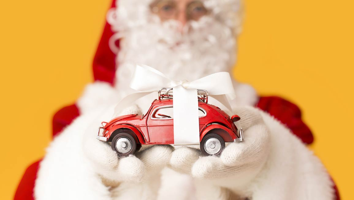 blurred-santa-claus-suggesting-toy-car-with-M8L6PR6