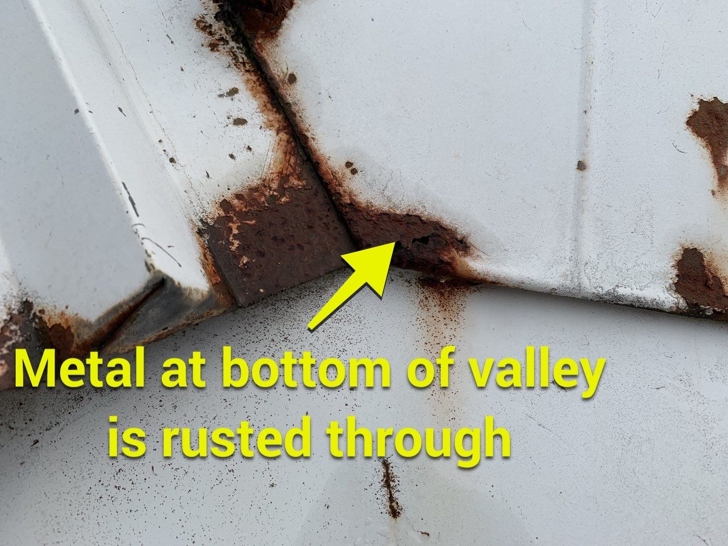 metal at bottom of valley is rusted through
