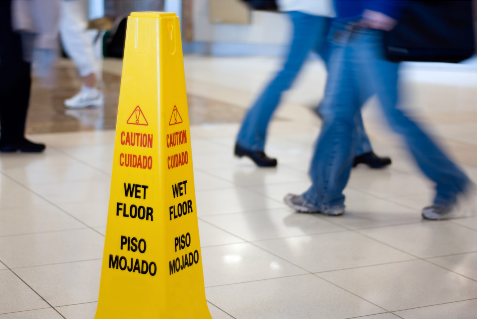 Caution Wet Floor sign with people walking in the background. Understanding Slip and Fall Accidents and Negligence Law Suits in Georgia.