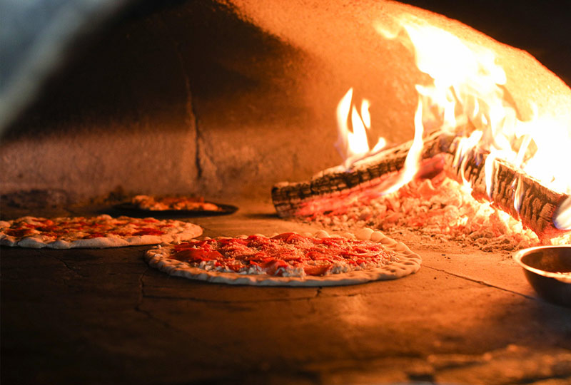 A photo of a freshly made pizza in a brick oven with coal and natural wood burning next to it.