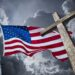 American flag with a christian cross and dramatic clouds.