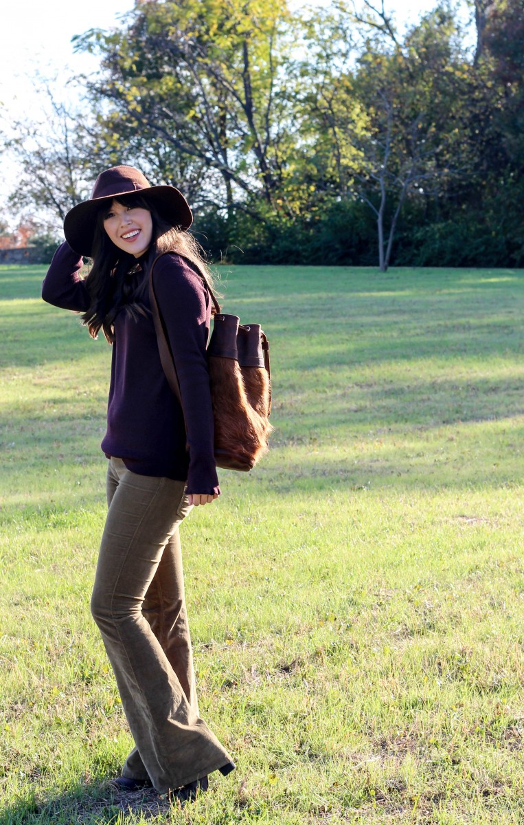 Lily Clair bag featured by top US fashion blog, Never Without Lipstick: image of a woman wearing a Lily Clair bag, a Target turtleneck, Saks Off Fifth wide brim hat, Free People flares and Target suede booties