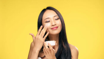 1045364 Woman puts cream on face on yellow background