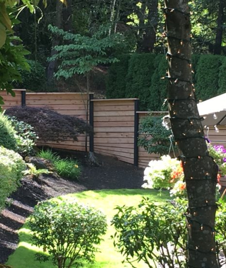 Stepped cedar fence with black posts
