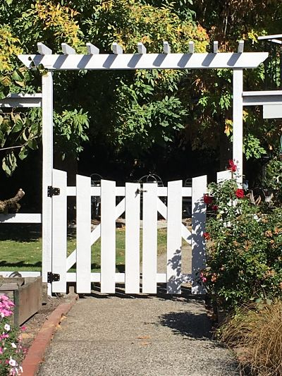 White arbor with white picket gate